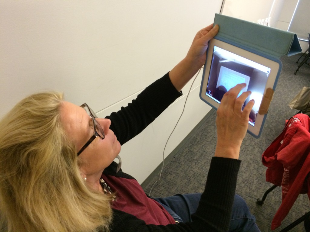 Photo of female using an iPad to record what presenter projected on the screen